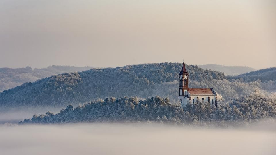 A church stands above a layer of fog at the village of Soshartyan, 115 kms northeast of Budapest, Hungary. (Peter Komka / MTI via AP)