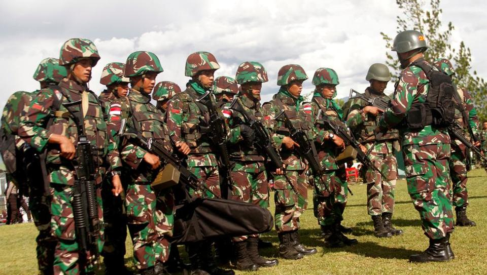Indonesian soldiers hold rifles as they pray before flying a helicopter to Nduga district in Wamena, Papua province, Indonesia, December 5.