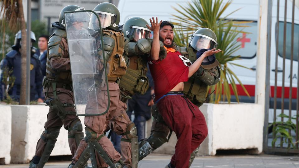 A Chilean dockworker is detained by riot police during a protest against port operator TPS (South Pacific Terminal), to demand temporary workers be included in collective bargaining, in Valparaiso, Chile. (Rodrigo Garrido / REUTERS)
