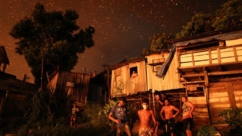 Residents of Educandos neighbourhood remain outside their houses, as firefighters try to control a massive fire, in Manaus, Amazonas state, Brazil. The fire destroyed at least 600 houses and its origin is still unknown. (Michael Dantas / AFP)