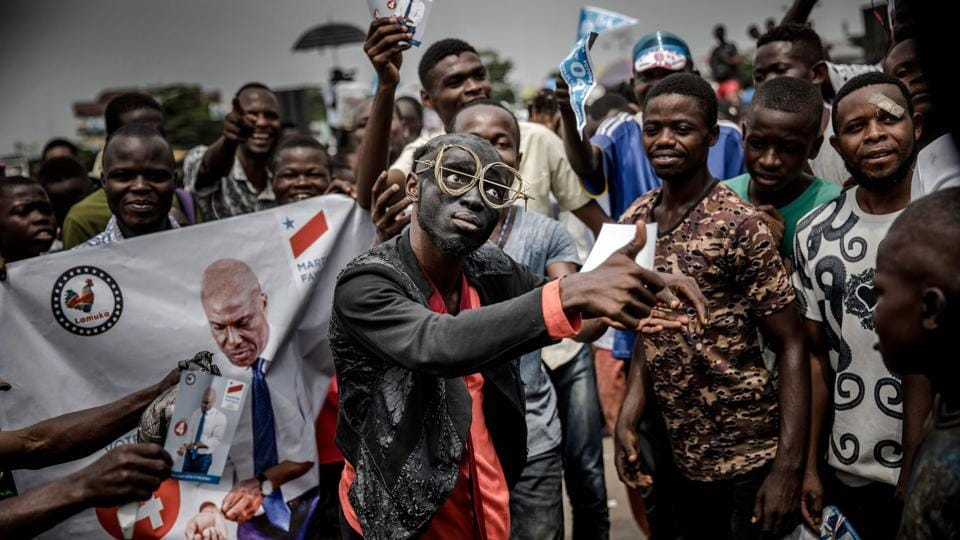 Supporters of opposition leader Martin Fayulu sing and dance as they march and chant slogans in the streets of the Ndjili district of Kinshasa, ahead of a campaign rally for Democratic Republic of Congo's general elections. (Luis Tato / AFP)