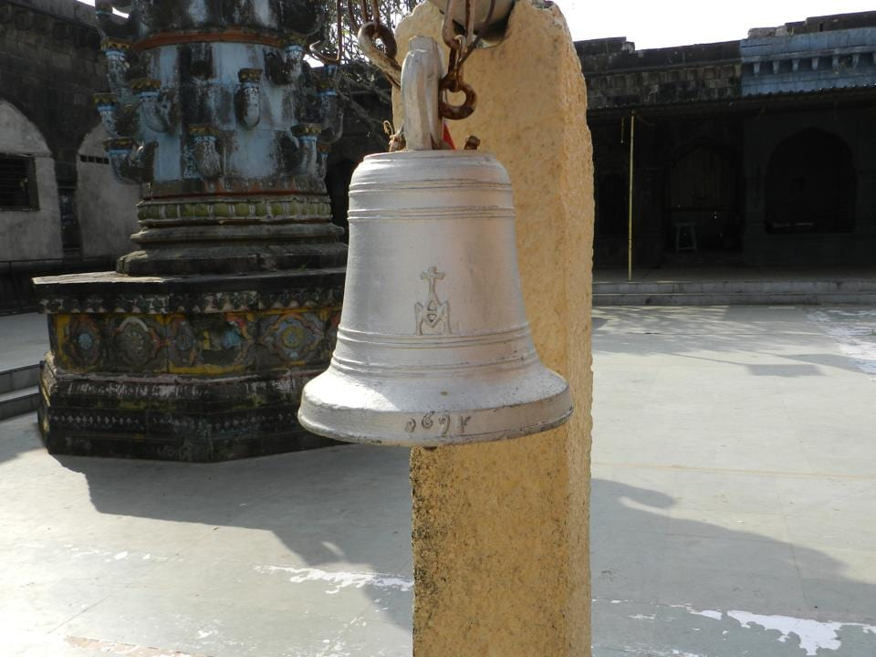 A bell at the Nimgaon Khandoba temple in Pune district with a crucifix on it.