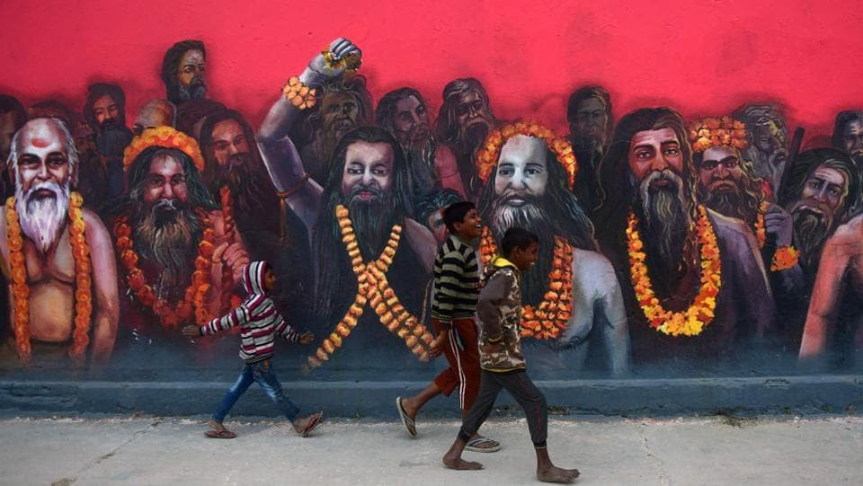 Children walk past a mural of sadhus on the wall of a temple, created as part of the ongoing 'Paint My City' project for the upcoming Kumbh Mela festival, in Prayagraj, Uttar Pradesh. (Sanjay Kanojia / AFP)