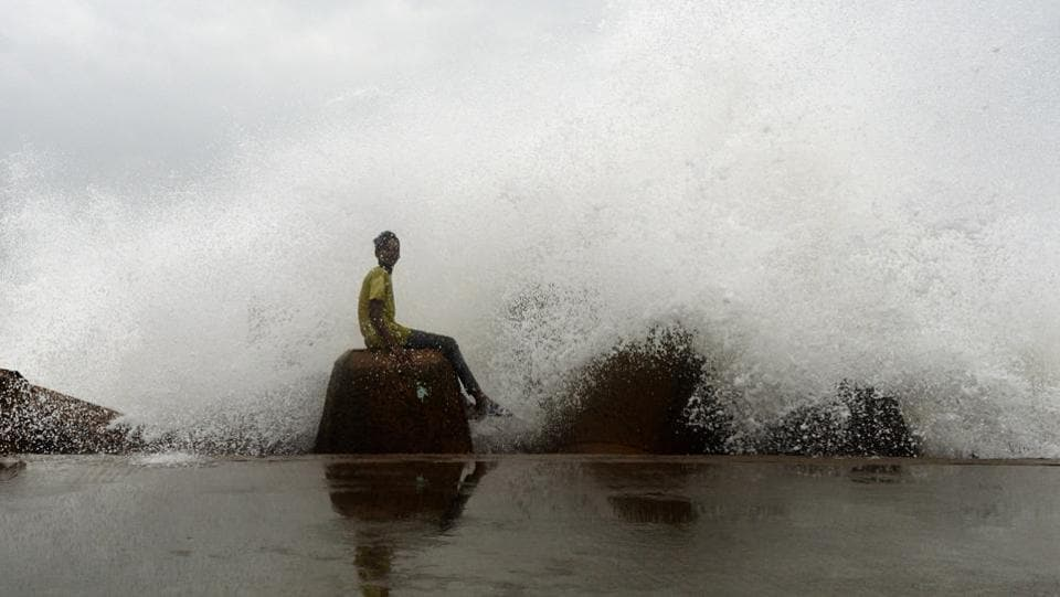 A young boy sits on a concrete block as waves hit a breakwater at Kasimedu fishing harbour, as cyclone Phethai approaches the eastern Indian coast, in Chennai, Tamil Nadu. (Arun Sankar / AFP)