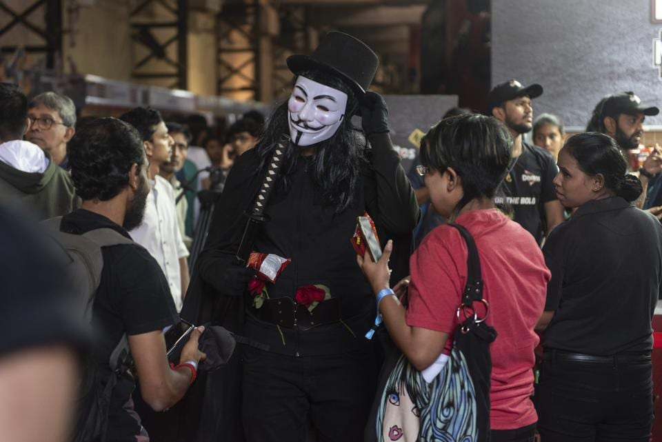 Fans interact with a person dressed as the eponymous protagonist from alan Moore's graphic novel, V for Vendetta.