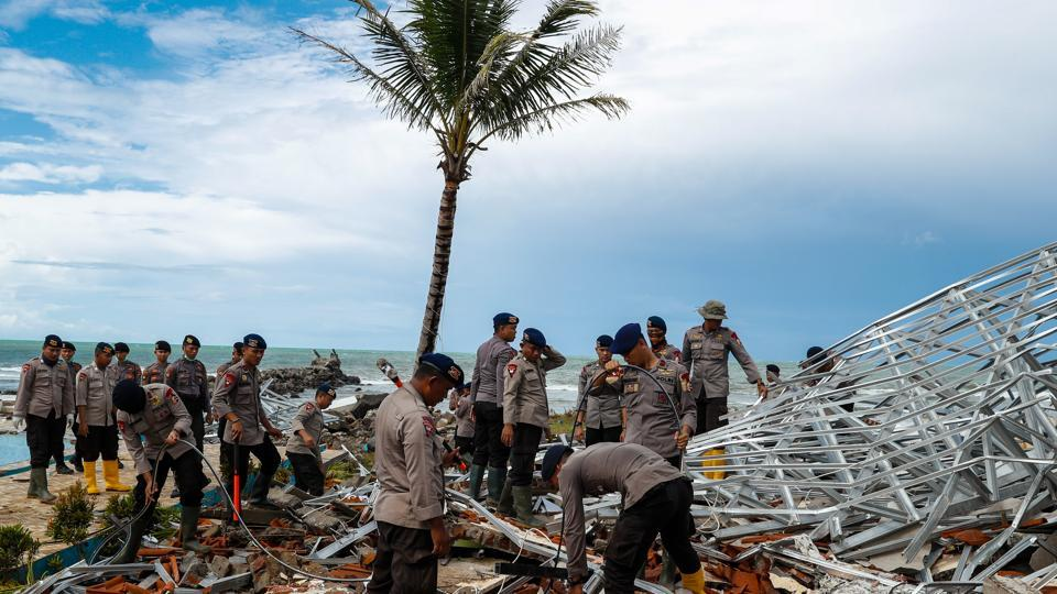 Police officers search for victims among rubble of a destroyed beach front hotel, which was hit by a tsunami in Pandeglang, Banten province, Indonesia, December 24, 2018.