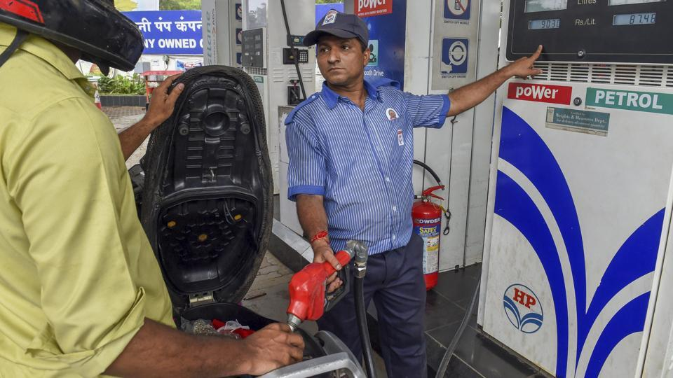 An employee shows the revised prices of petrol and diesel to a customer at a fuel station in Mumbai