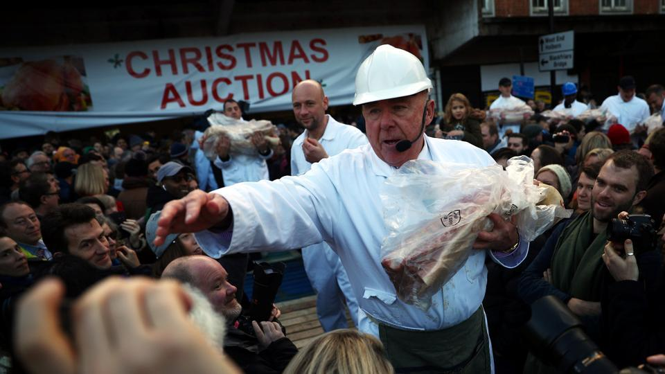 Butchers hold up cuts of meat during a Christmas Eve auction in Smithfield market in London, England. Hoards of punters gathered to bid on last-minute meats for their Christmas meal at the 150-year-old open-air auction. (Hannah McKay / REUTERS)