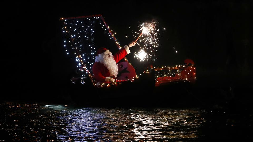 A festive spirit marked Christmas celebrations across the world with thousands of people visiting churches and offering prayers with some last-minute shopping thrown in the mix. Seen here is a man dressed as Santa Claus holding a flare on a boat during Christmas Eve celebrations in Imperia, Italy. (Antonio Calanni / AP photo)