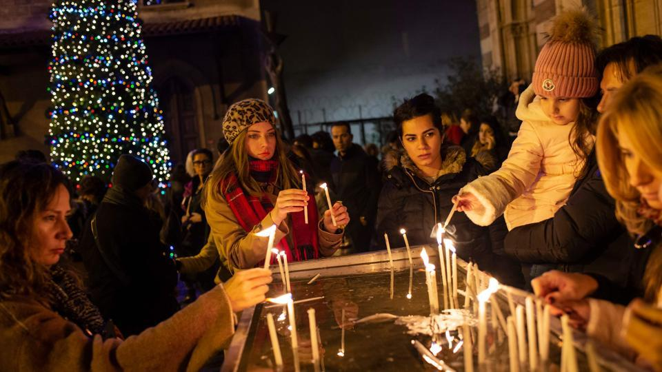 Worshippers light candles as they attend Christmas Mass at the Saint Antuan Church in Istanbul, Turkey on Christmas Eve. (Yasin Akgul / AFP)