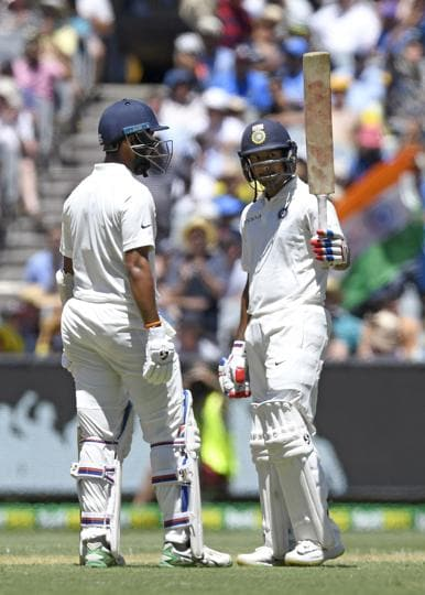 India's Mayank Agarwal, right celebrates with team mate, left Cheteshwar Pujara after scoring a half century on day one of the third cricket test between India and Australia in Melbourne. (AP)