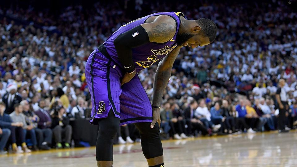 LeBron James #23 of the Los Angeles Lakers leans over in pain after he was hurt against the Golden State Warriors during the second half of their NBA Basketball game at ORACLE Arena.