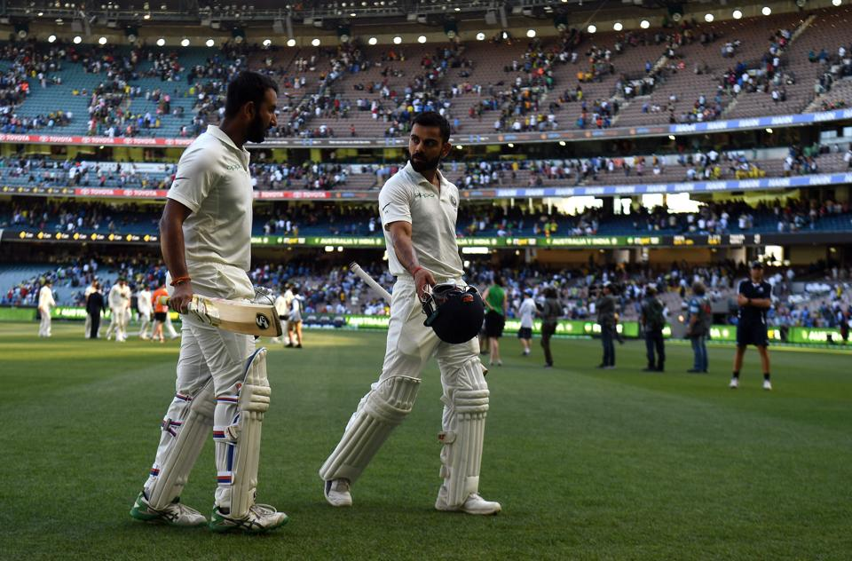 India's batsmen Virat Kohli (R) and Cheteshwar Pujara walk back to the pavilion at the end of play on the day one of the third cricket Test match between Australia and India in Melbourne . (AFP)