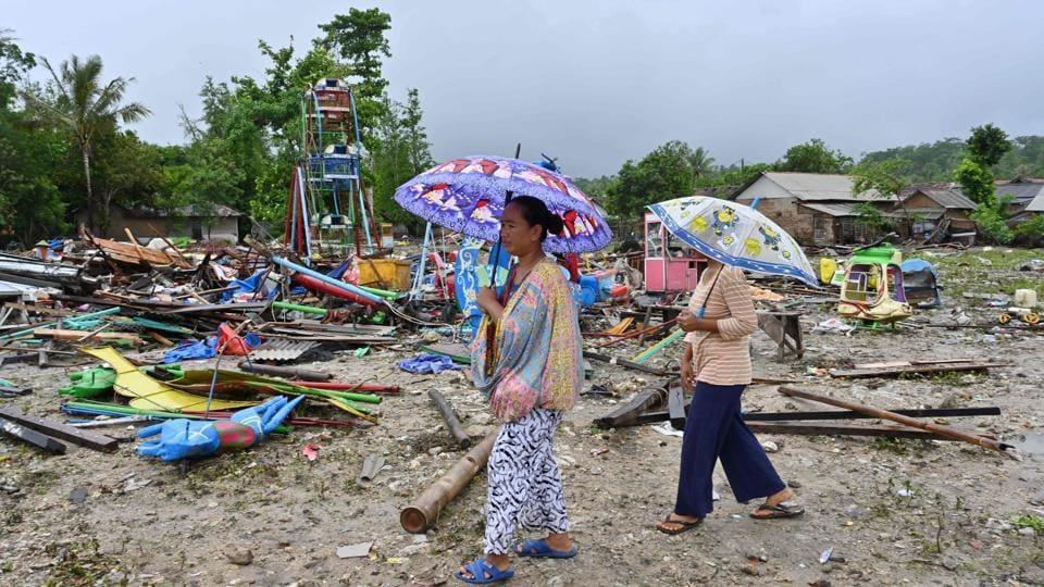 Hartati (L), whose house was destroyed by the tsunami, walks with a relative in the Sumber Jaya village in Sumur, Banten province. (Adek Berry / AFP)
