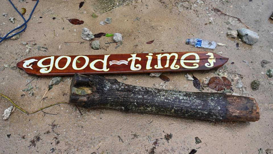 "A wooden sign that read ""Good Times"" lies on the ground. At the Tanjung Lesung resort, cars and minibuses had been thrown against buildings, concrete walls cracked into small pieces and trees uprooted. More than 200 workers from the state electricity company were watching pop band ""Seventeen"" perform when the tsunami struck leaving only the four-member band's lead vocalist alive. (Adek Berry / AFP)"
