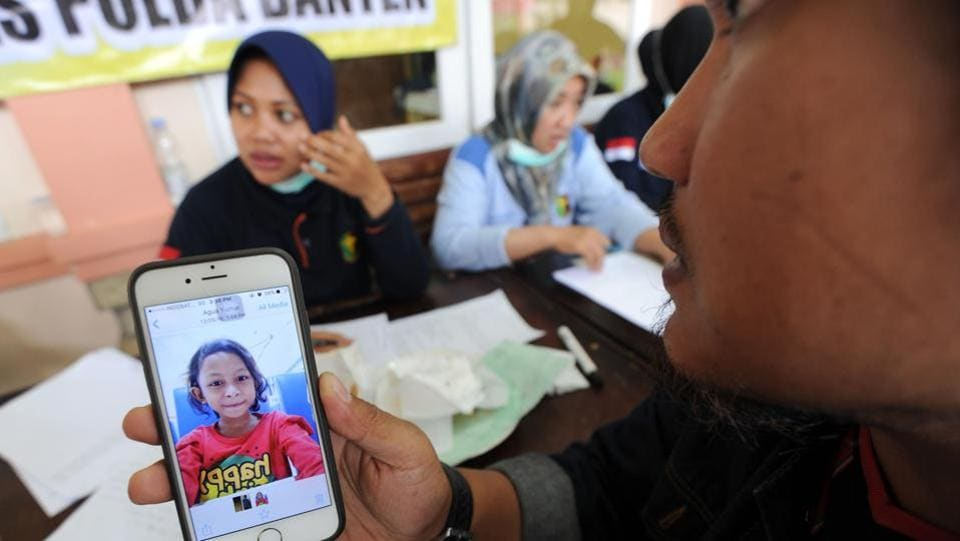 An Indonesian relative shows a picture from a phone to an officer at an identification centre in Pandeglang, Banten province. Arifin Hadi, head of disaster management at the Indonesian Red Cross said that their teams are seeing many broken bones and broken homes, and people who are very shaken. (Sonny Tumbelaka / AFP)
