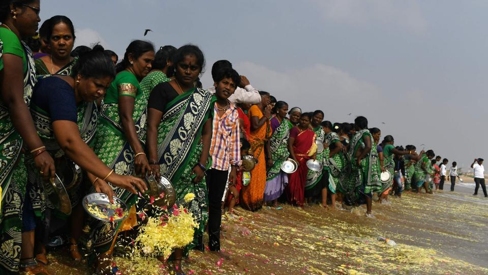 Women throw flowers into the sea as an offering during a ceremony for the victims of the 2004 tsunami at Pattinapakkam Beach in Chennai on December 26.