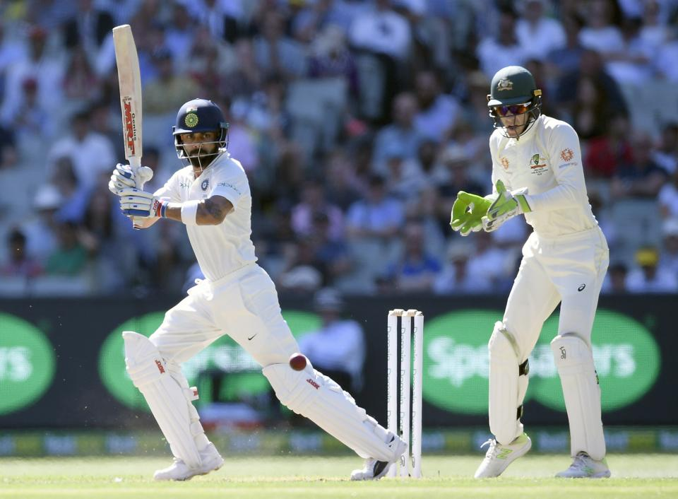 India's Virat Kohli, left and Australia's Tim Paine during play on day one of the third cricket test between India and Australia in Melbourne. (AP)