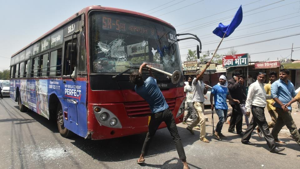 Members of a Dalit organisation damage a bus during Bharat Bandh in Bhopal, Madhya Pradesh. Several Dalit groups had called for a 'Bharat Bandh' in April, demanding restoration of the Scheduled Castes/Scheduled Tribes (Prevention of Atrocities) Act to its original form. The Bandh was a call highlighting latent resentment among the community. (Mujeeb Faruqui / HT Photo)