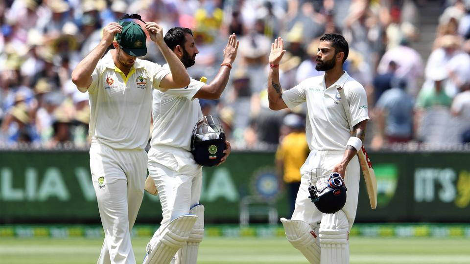 India's batsmen Cheteshwar Pujara (C) and Virat Kohli (R) walk back at lunch during day two of the third cricket Test match between Australia and India in Melbourne on December 27, 2018.