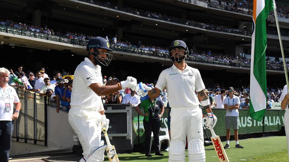 India's batsmen Virat Kohli (R) and Cheteshwar Pujara walk out to resume batting on day two of the third cricket Test match between Australia and India in Melbourne. (AFP)