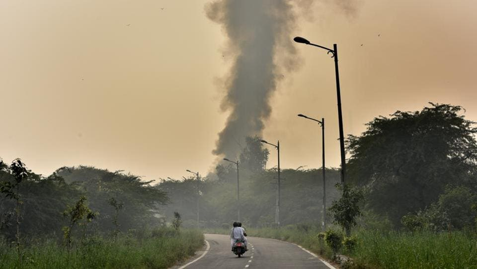 A heap of dry leaves and discarded waste material raises a plume of smoke after catching fire, behind Rajghat, in New Delhi. Despite pre-emptive bans on crackers, stubble burning in neighbouring states and halts on construction activity pollution levels still climbed to hazardous levels as the winter months approached Delhi. (Sonu Mehta / HT Photo)