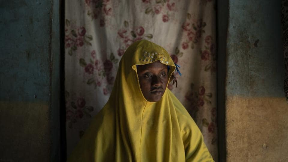 Mariama Konte wears a widow's veil in a village near Goudiry, Senegal. Barely 20 years old, Konte was neither widow nor wife. For nearly four years, she told her two young children that their father is travelling for work. Only in the last few weeks has she begun to accept the possibility that Abdrahamane drowned at sea, like so many migrants from this dusty corner of eastern Senegal. (Felipe Dana / AP)