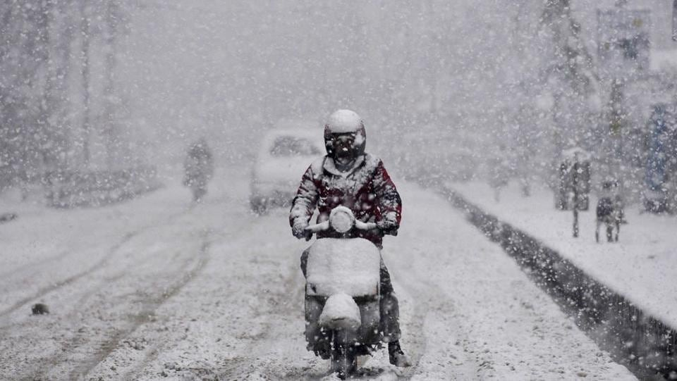 A man rides a scooter while it snows heavily in Srinagar, Jammu and Kashmir. (Waseem Andrabi / HT Photo)