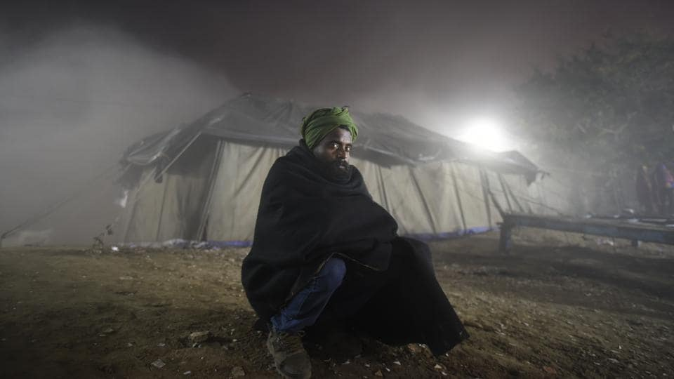 A homeless man poses for a picture during a movie screening in a temporary open-air theatre on the eve of New Year near Nigambodh Ghat, in New Delhi. Delhi's infamous winter has made itself apparent this year, breaking a 15-year record for lowest temperatures so far. (Burhaan Kinu / HT Photo)