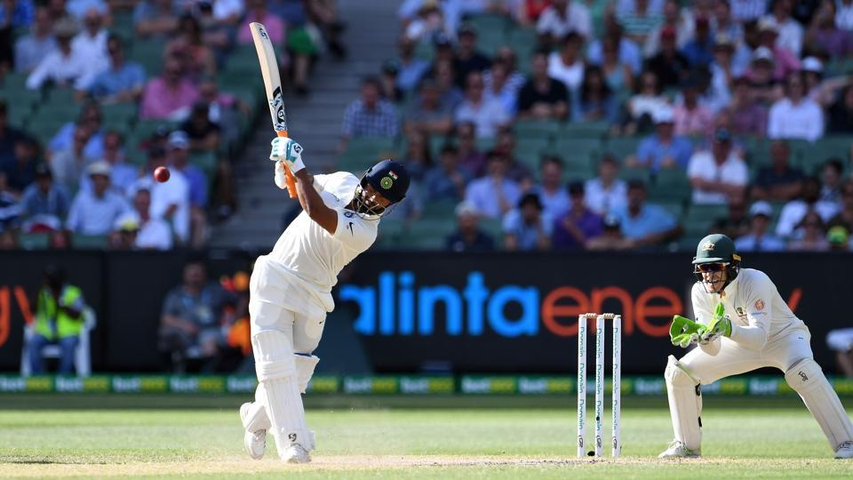India's batsman Rishabh Pant plays a shot as Australia's wicketkeeper Tim Paine (R) looks on during day three of the third cricket Test match between Australia and India in Melbourne on December 28, 2018.