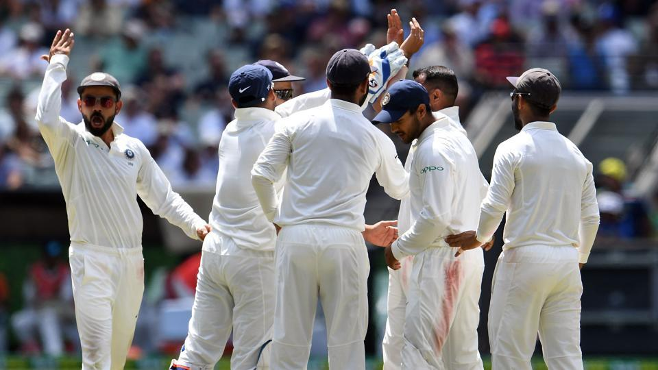 Indian cricketers celebrate the dismissal of Australia's batsman Pat Cummins during day three of the third cricket Test match between Australia and India in Melbourne. (AFP)