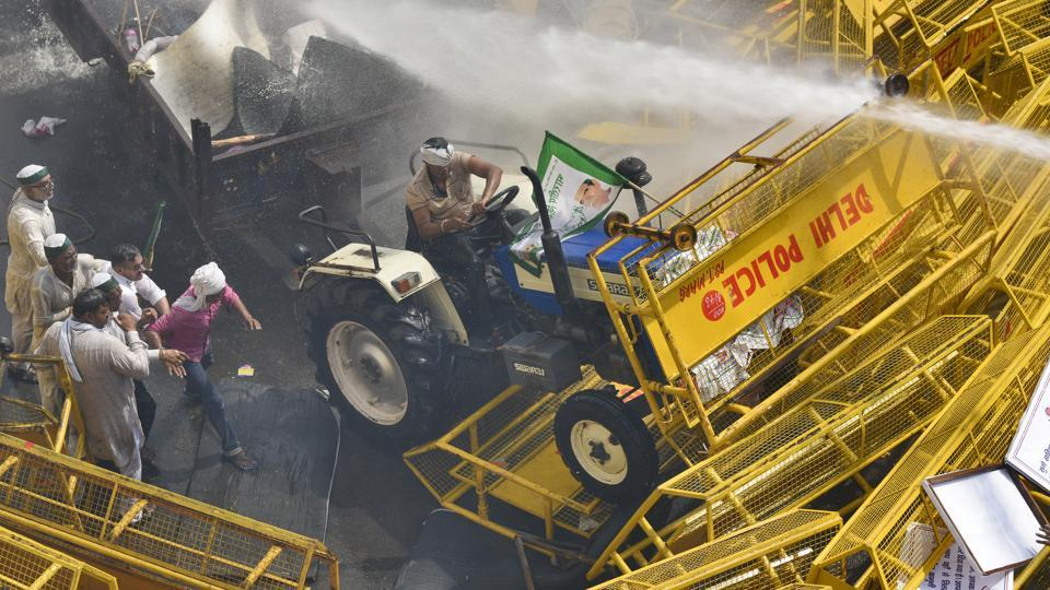 A farmer drives his tractor into barricades as a massive rally clashed with police and paramilitary forces, prompting police to use tear gas and water cannons to stop the protesting farmers, attempting to enter the national capital from Uttar Pradesh to seek better prices and concessions from entering the city, at Delhi-Ghaziabad border. (Burhaan Kinu / HT Photo)