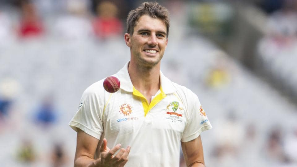 Australia's Pat Cummins tosses Travis Head ball up as he returns to his bowling mark during play on day three of the third cricket test between India and Australia in Melbourne.