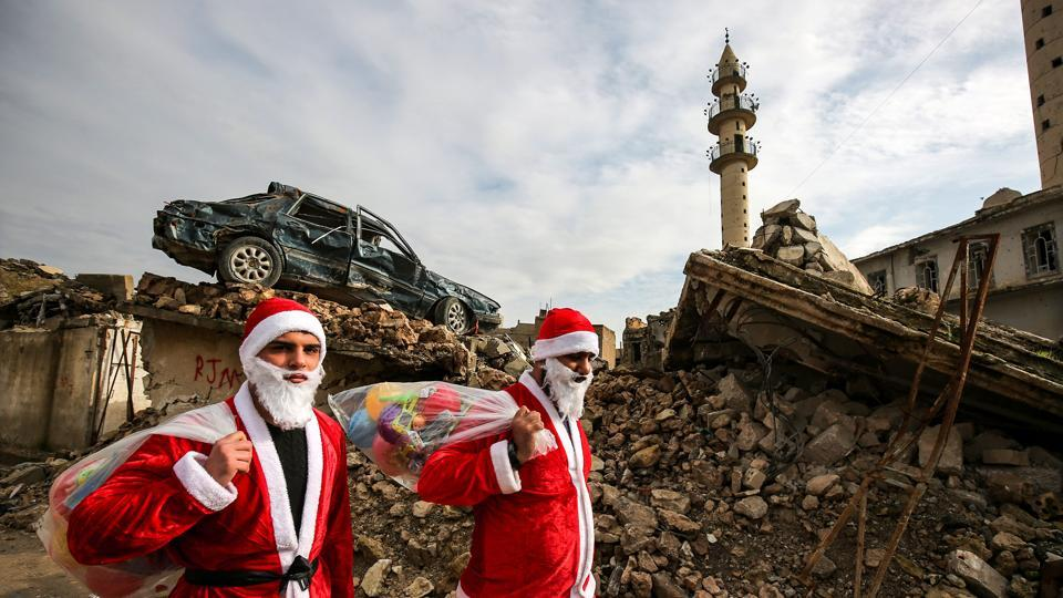 Iraqi youths dressed in Father Christmas suits walk through the streets of the old city of Mosul as they distribute gifts. (Ahmad Al-rubaye / AFP)