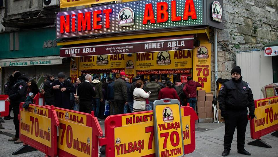 """A security staff member stands guard as people queue to buy lottery tickets at the Nimet Abla lottery stand in Istanbul. Each year in the run-up to the New Year draw, thousands of people flock to the most famous lottery stand in Istanbul, drawn by the promise on display: """"Nimet Abla will make you win."""" (Yasin Akgul / AFP)"""