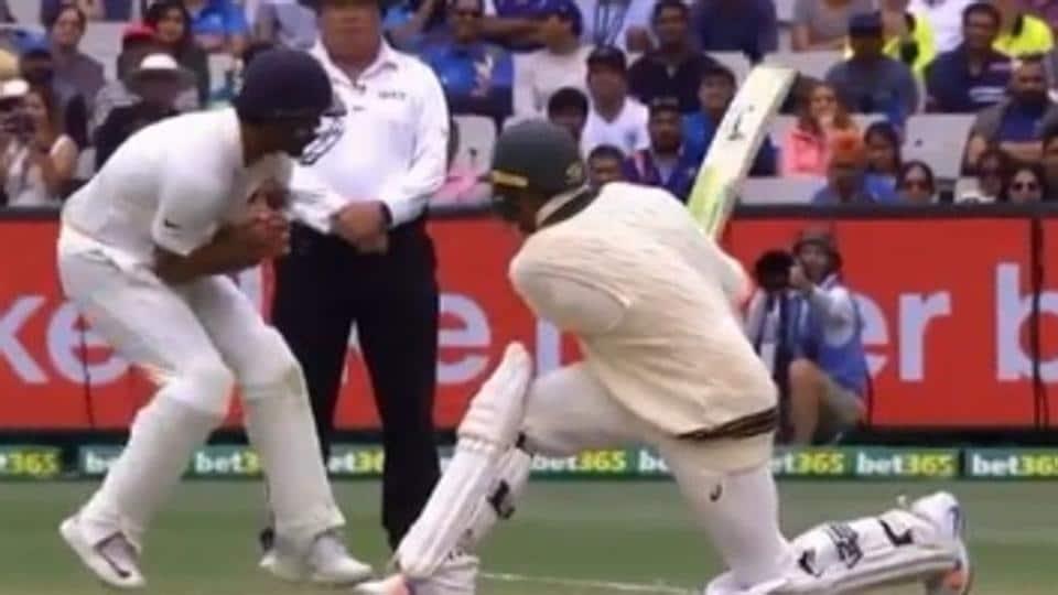 Usman Khawaja hits a ball as Mayank Agarwal tries to get out of the way.