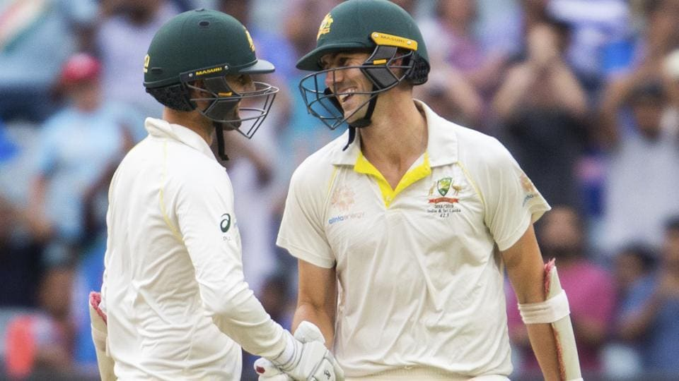 Australia's Nathan Lyon, left, shakes hands with Pat Cummins after cummins reached his 50 during play on day four of the third cricket test between India and Australia in Melbourne. (AP)