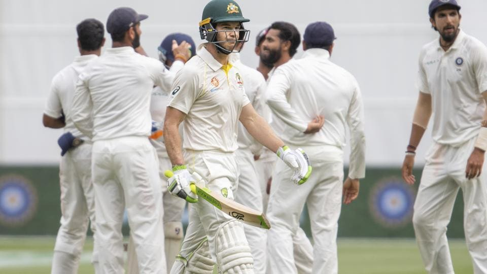 Australia's captain Tim Paine, center, walks off after being caught out during play on day four of the third cricket test between India and Australia in Melbourne. (AP)