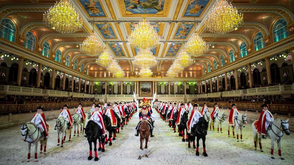 """Riders and horses perform in the show hall of the equestrian-themed """"Pegasus Water Town"""" in Jiangyin, China. Leather riding boots neatly lined up, a picture of hounds on a fox hunt and a fountain spewing water from the mouths of stone horses. It may have the trappings of upper-class Britain, but is in fact the County Down Club, the self-styled first exclusive membership club in China for horsemanship and fox-hunting. (Johannes Eisele / AFP)"""