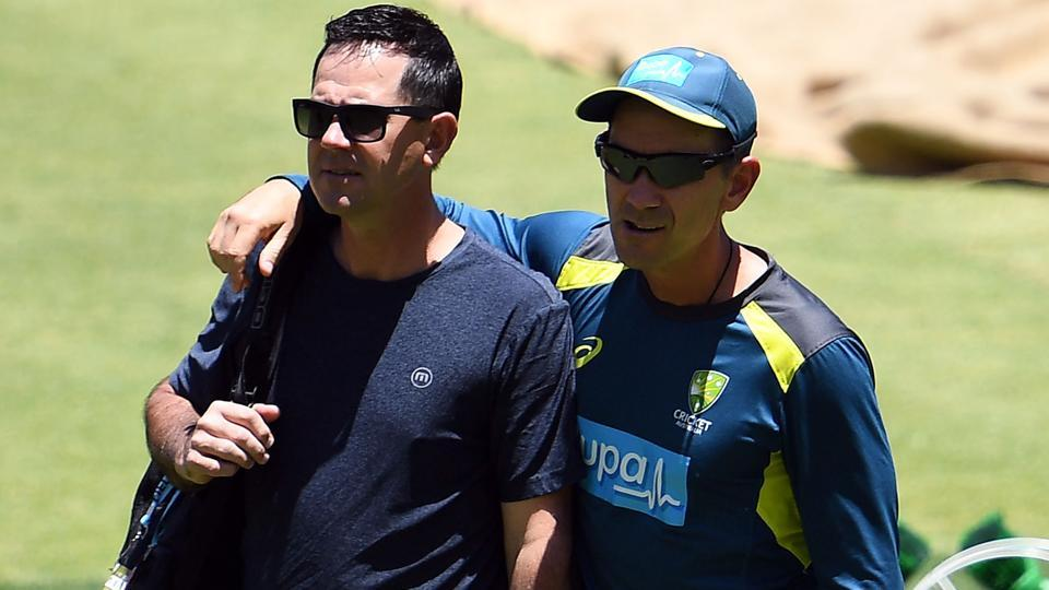 Ricky Ponting (L) and Australia's coach Justin Langer walk in the ground.