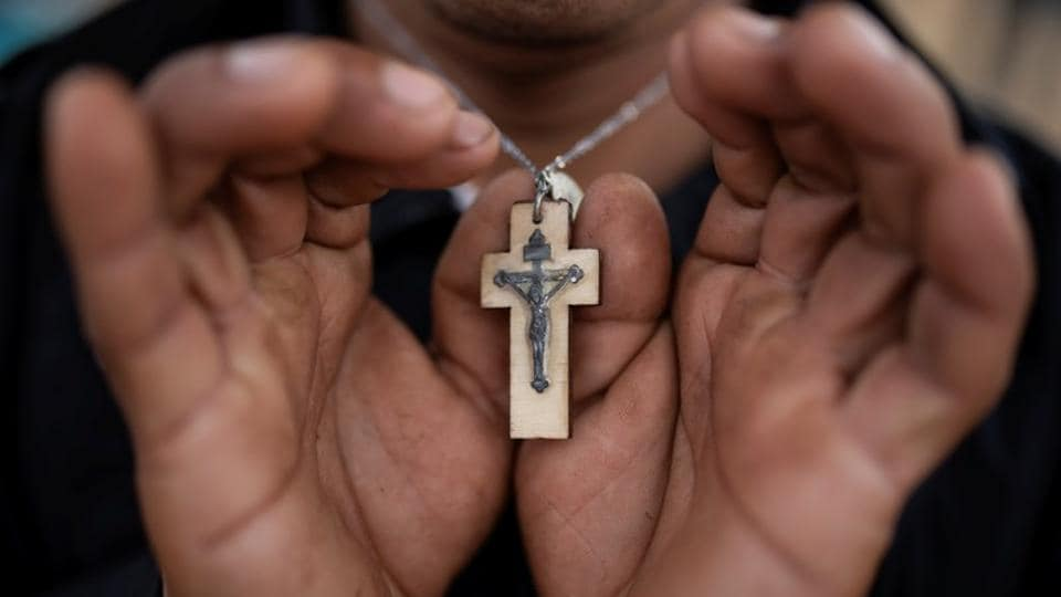 """Since setting out from Honduras in the hope of reaching the United States, Nicolas Alonso Sanchez has worn a simple wooden cross around his neck – a quiet reminder of the Roman Catholic faith that propels him forward. """"God gave me the strength to get all the way here,"""" said Sanchez. On the long journey from Central America to US soil, many migrants have taken solace in religion. (Alkis Konstantinidis / Reuters)"""