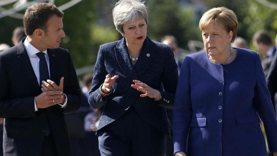 British Prime Minister Theresa May (C), German Chancellor Angela Merkel (R) and French President Emmanuel Macron.