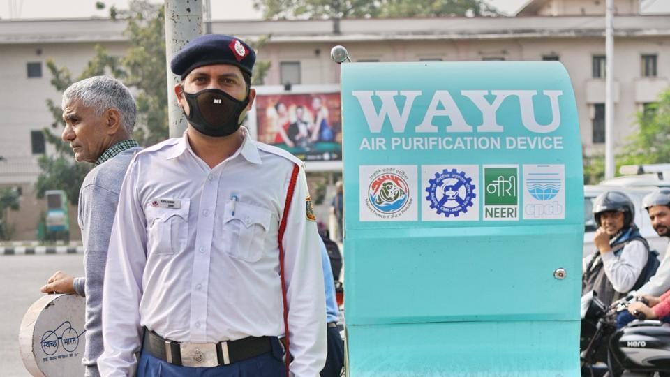 A traffic police officer stands next to the WAAYU Air Purifiers installed by government of Delhi at ITO, New Delhi. The city's air quality in December was the foulest since 2015.
