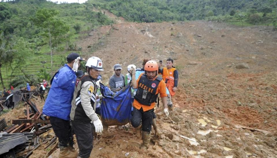 Rescuers carry the body of a landslide victim in Sirnaresmi, West Java, Indonesia, Tuesday, Jan. 1, 2019. The landslide triggered by torrential rain has killed a number of people and left dozens of others missing on Indonesia's main island of Java.