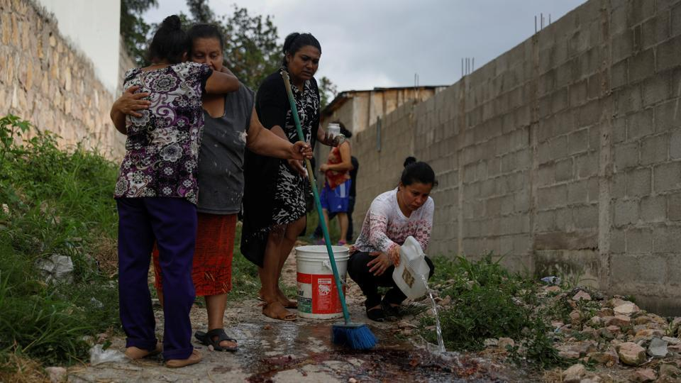 Ana Luz, a sister-in-law of Ronald Blanco, looked on grimly as neighbours of the murdered Honduran man washed away the rills of blood left where his bullet-ridden body had lain outside his house in a troubled barrio on the outskirts of Tegucigalpa. (Edgard Garrido / REUTERS)