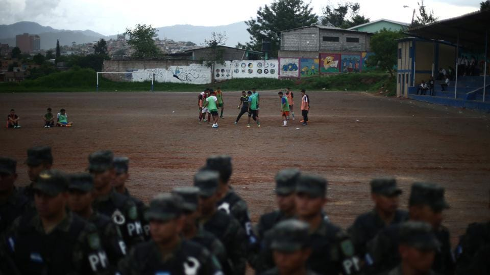 Men play soccer as soldiers line up in a neighbourhood occupied by gangs known as El Hoyo in Tegucigalpa. Danger in Honduras is never far away. For comparison, the latest statistics in the United States state there were 5.3 murders per 100,000 in 2017, according to the FBI's most recent report on its website. (Edgard Garrido / REUTERS)