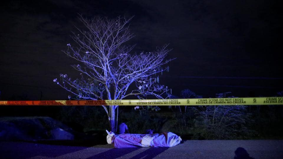 The body of a man lies on a highway in San Pedro Sula, Honduras. According to Honduran government figures, the homicide rate reached 86 per 100,000 people in 2011-2012. The rate for 2018 should end below 40 per 100,000, the security ministry has said. (Edgard Garrido / REUTERS)
