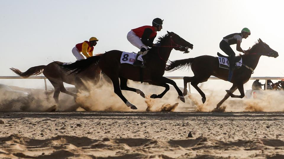 Jockeys ride their horses as they participate in a race during the festival. The festival also features a classic cars show and a fireworks display. (Karim Sahib / AFP)