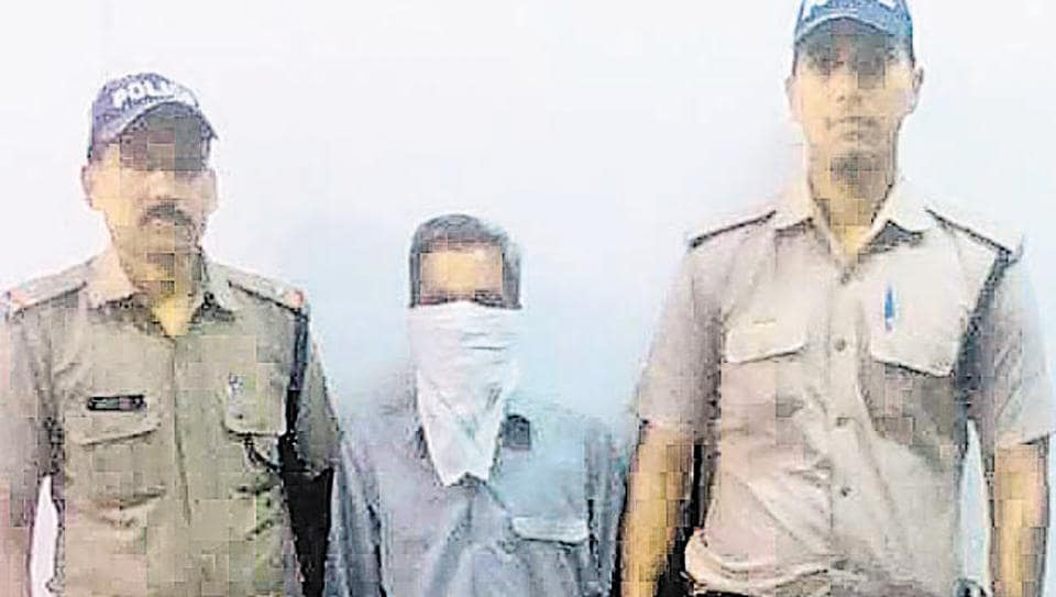 Suresh Singh (with covered face) in police custody.