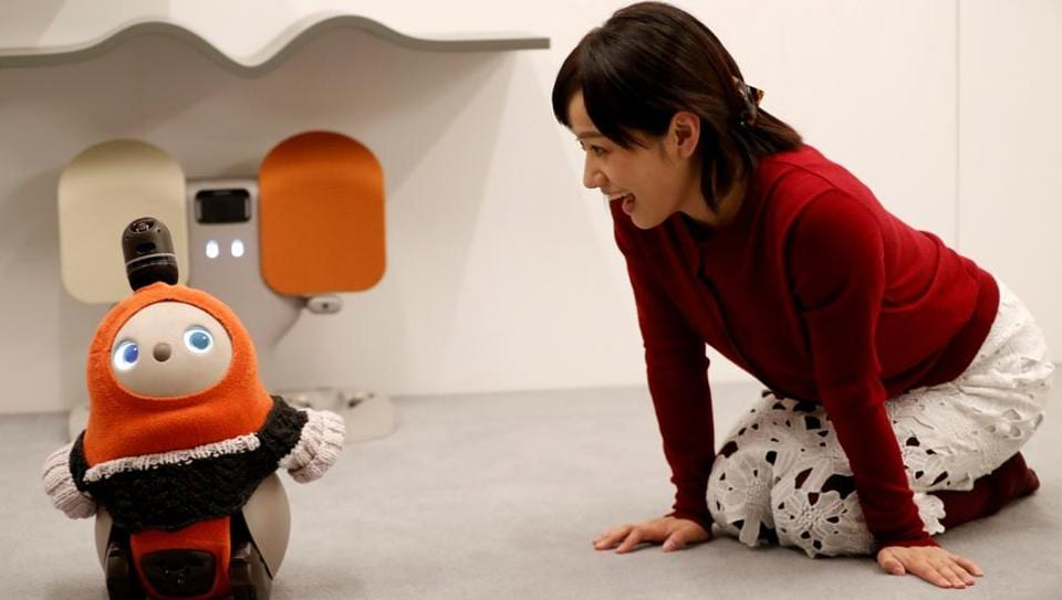 A woman calls up GROOVE X's new home robot LOVOT at its demonstration during the launching event in Tokyo, Japan, December 18, 2018.